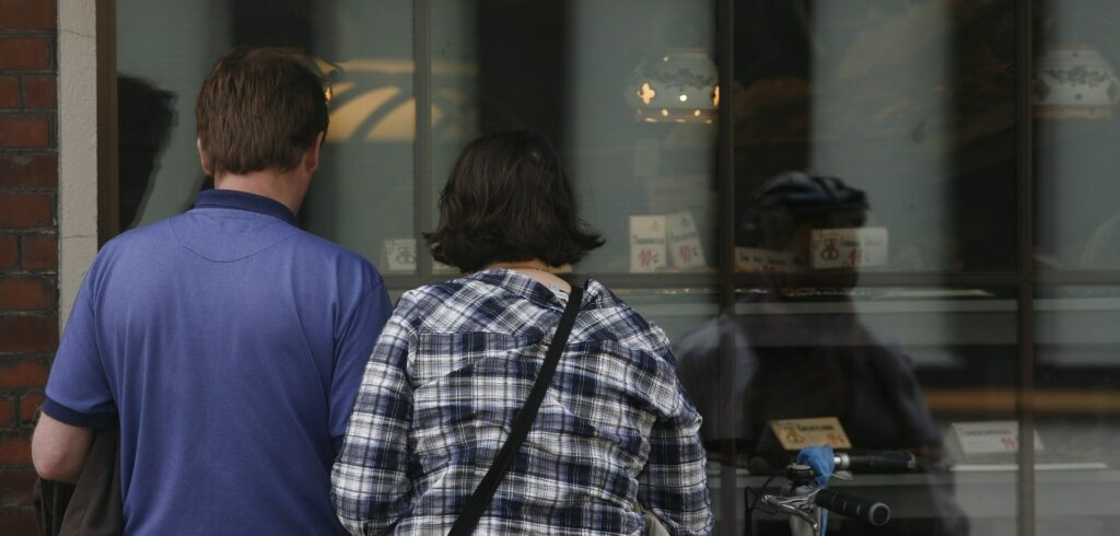 man and woman gazing through Baytown commercial glass storefront